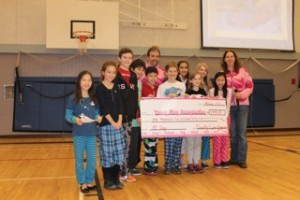 """School children donating a cheque to Team Finn after holding a """"PJs With a Purpose"""" Day"""